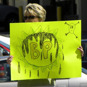 A  protestor holds up her own version of the BP logo, dripping with oil.